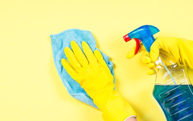 Des mains gantées nettoyant un mur