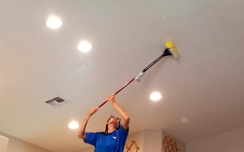 Personne des services de nettoyage professionnels nettoyant un plafond