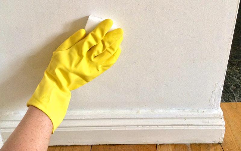 Main gantée nettoyer un mur