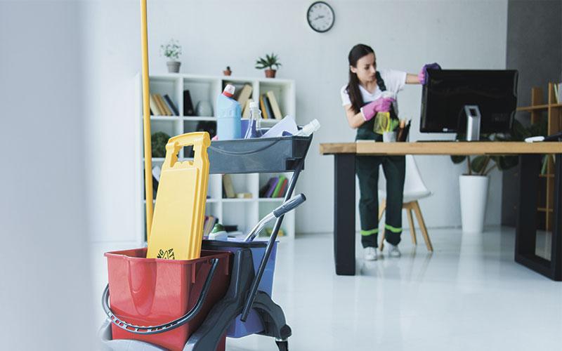 Service de nettoyage professionnel femme dépoussiérant un téléphone de bureau