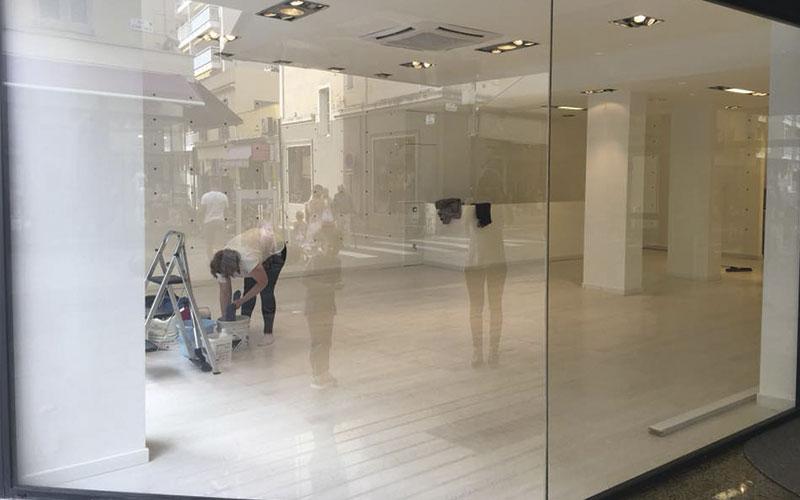 Concierge nettoyant les planchers et les fenêtres d'un magasin rénové