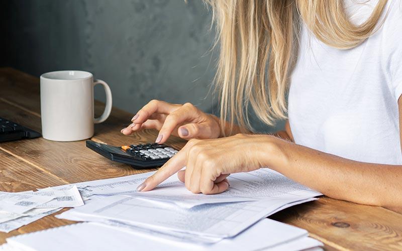 Femme estimant la facture de nettoyage avec une calculatrice